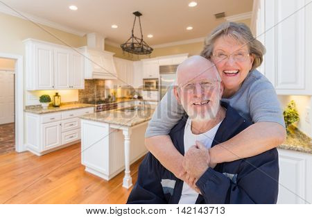 Happy Loving Senior Couple Hugging Inside Custom Kitchen.