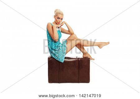 Beautiful sexy tanned barefoot pin-up girl in stylish dress sitting on big vintage bag over white background