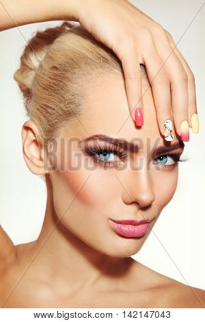 Close-up portrait of young beautiful blonde woman with stylish fresh make-up and fancy manicure