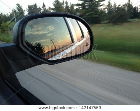 View of the sunset from the rear view mirror