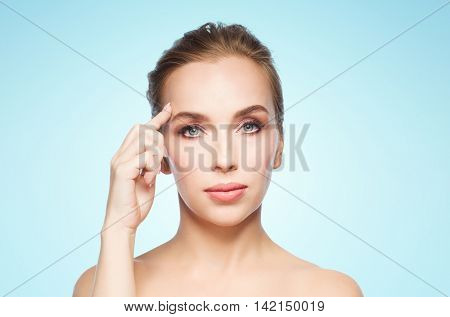 beauty, people and plastic surgery concept - beautiful young woman showing her forehead over blue background