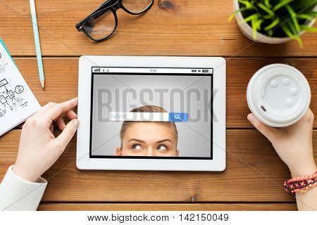 business, education, technology, people and internet concept - close up of woman with internet browser search bar on tablet pc computer screen and coffee on wooden table