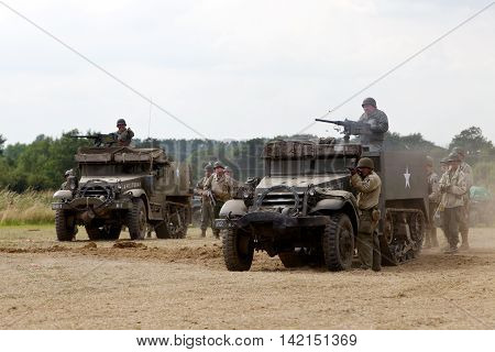 WESTERNHANGER, UK - JULY 21: Two WW2 US halftracks supported by infantry advance on German forces during a battle re-enactment at the War & Peace Revival show on July 21, 2016 in Westernhanger