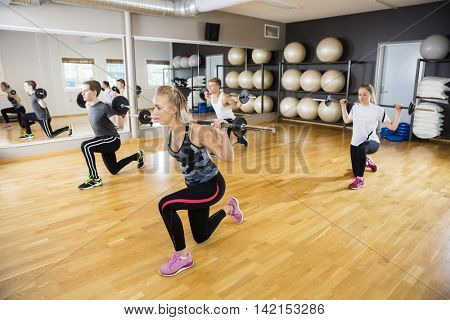 Friends Lifting Barbells On Hardwood Floor In Gym