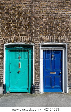Two painted exterior wooden doors next to each other. Traditional style.