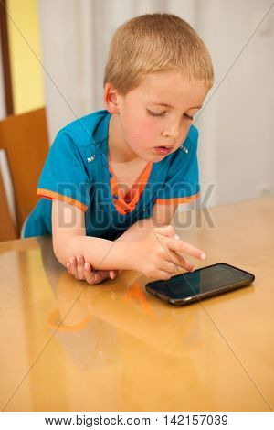 Young boy plays with a smart phone