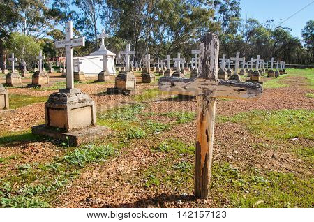 NEW NORCIA,WA,AUSTRALIA-JULY 15,2016: Rows of headstones with crosses and upright grave monument in cemetery in the monastic town of New Norcia, Western Australia.