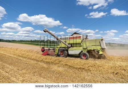 Working combine harvester during harvest on a grain field
