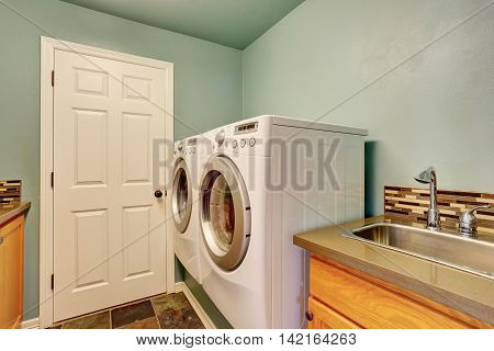 Mint Laundry Room With White Appliances And Sink