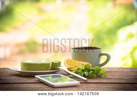 Background fruit  and coffee cup with green tea cake and mint with smartphone.On wooden background outdoor view and holiday with relax .
