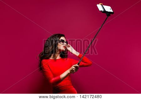 Portrait of beautiful brunette in awesome dress and red lips wearing sunglasses while making selfie with stick. Isolated. Retouched photo.