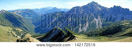 Mountains and valleys in the Allgäu Alps in Tyrol, Austria;  rugged summit, deep valleys, mountain meadows, sunny day, panoramic