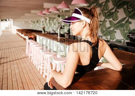 Young beautiful sports woman resting after workout in a beach cafe on palm leaves pattern background