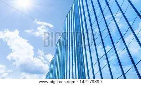 Perspective and underside angle view to textured background of contemporary glass facade of achitecture building skyscrapers with the light reflect of sky and cloud. (Detail curve shape of glass with vertical and horizontal mullion)