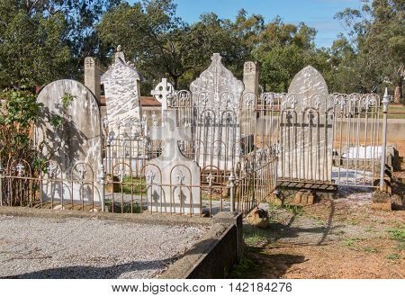 NEW NORCIA,WA,AUSTRALIA-JULY 15,2016: Old cemetery with rear of fenced headstones in peaceful treed landscape in the monastic town of New Norcia, Western Australia.