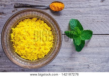 Top view of an antique metal bowl with cooked turmeric jasmine rice mint leaves and vintage teaspoon filled with powdered curcumin