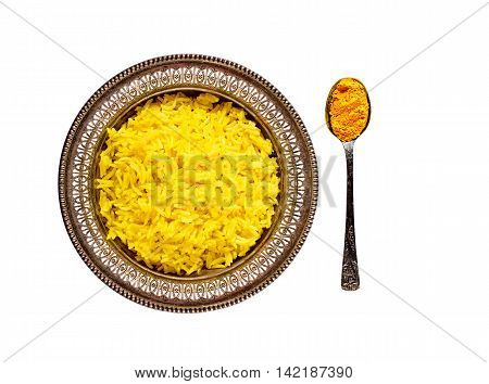 Top view of an antique metal bowl with cooked turmeric jasmine rice and vintage metal teaspoon with powdered curcumin isolated on white