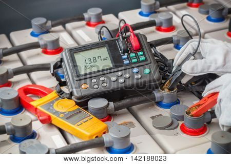 Electrician used digital battery tester measure voltage annd resistance of batteries bank system.