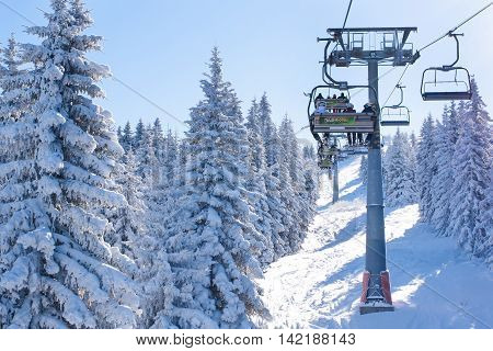 Kopaonik, Serbia - January 22, 2016: Ski resort Kopaonik, Serbia, people on the ski lift among the snowy white pine trees