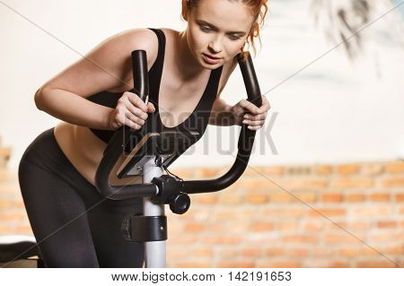 Active Young Woman Doing Exercise On Bicycle At Home