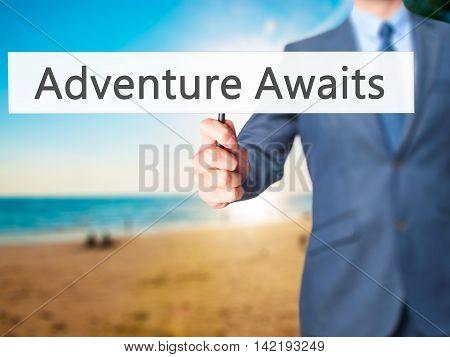 Adventure Awaits - Businessman Hand Holding Sign