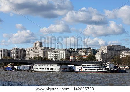 LONDON - OCTOBER 14: A small flotilla of commercial vessels and tourist boats stand moored out in the river Thames close to the landmark of Waterloo Bridge on October 14, 2012 in London.