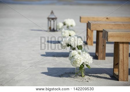 Detail of flowers in mason jars at beach wedding