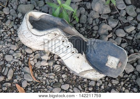 Dirty old shoes on a background of stones. Dirty and old shoes.