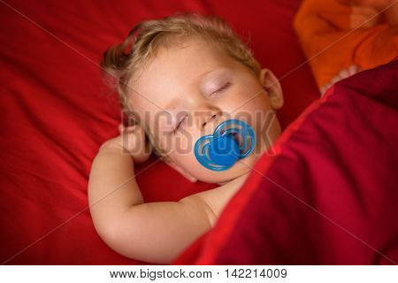 Infant boy eight month old sleeping with soother in his mouth in red background close up.