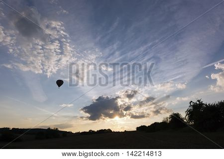 The sunset with clouds and silhouette of a hot air balloon