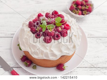 Sponge cake with whipped cream and raspberries on wooden background