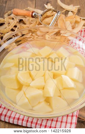 peeled and diced potatoes are in the glass bowl with water to to withdraw the potato starch