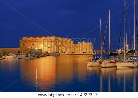 View of the medieval Venetian Castle and Heraklion port at sunset. Crete. Greece. Boats blurred motion on the foreground.