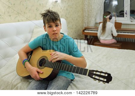two people in bedroom: boy holding guitar girl playing on synthesizer in background