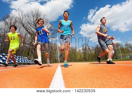 Bottom view of four multiethnic athletics teenage boys in sportswear running on the racetrack