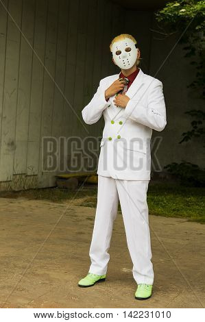 Lviv Ukraine - May 23.2015:Cosplayer boy posing in a white suit and a hockey mask photo taken at cosplayers meeting outdoor in Lviv city.May 23.2015