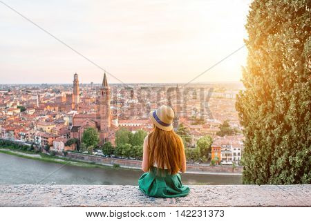 Woman enjoying beautiful view on Verona city in Italy on the sunset. Verona is famous city of love in the north of Italy.