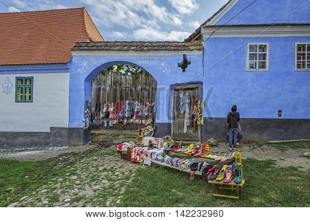 Viscri Romania - July 21 2016: Handmade wool and felt clothes designed by the locals exhibited in front of their houses on a narrow street of the Saxon landmark village in Transylvania.