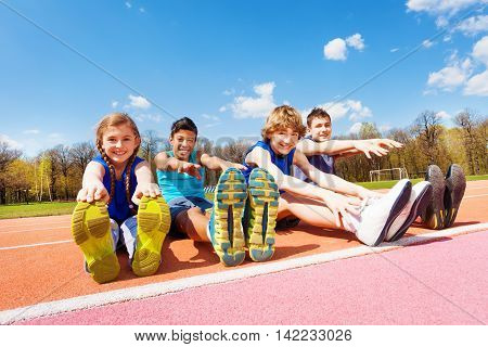 Portrait of four happy teenage kids sitting in a row doing stretching exercises outdoors on the stadium