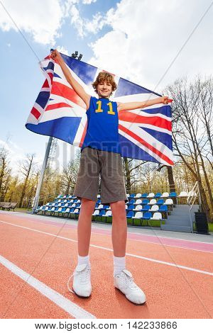Full-length portrait of happy smiling teenage boy in sportswear, holding flag of Great Britain behind him, outside in the stadium, bottom view