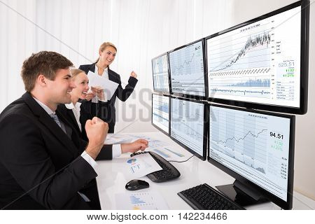 Happy Excited Male And Female Stock Market Brokers Looking At Graphs On Multiple Computer