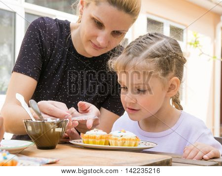 Mother Pours A Bag Of Confectionery Posypku On Easter Cupcake, Daughter Happily Looking