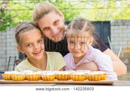 Mother Hugging Her Daughters Who Cook Delicious Cupcakes