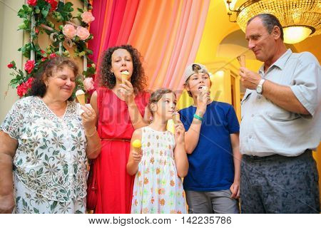 happy grandmother, grandfather, mother and children eating ice cream in store
