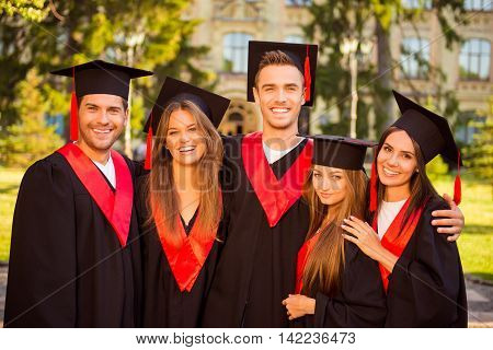 Successful Joyful Five Graduates In Robes And Hats Smiling And Hugging