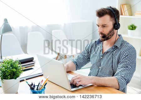Young Operator Of Call Center With Head-phones Work With  Laptop
