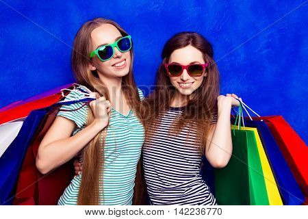 Portrait Of Two Beautiful Women In Glasses With Colorful Paperbags