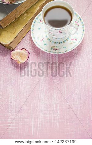 A cup of coffee rose petal and old books. Copy space background