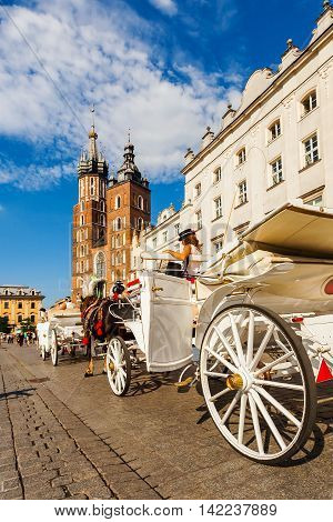 Church of St. Mary in the main Market Square with beautifully decorated horse and white old coach in the foreground. Basilica Mariacka. Krakow. Poland.