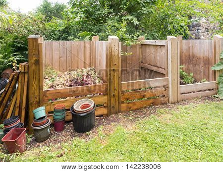 wooden compost bins in garden setting with foliage